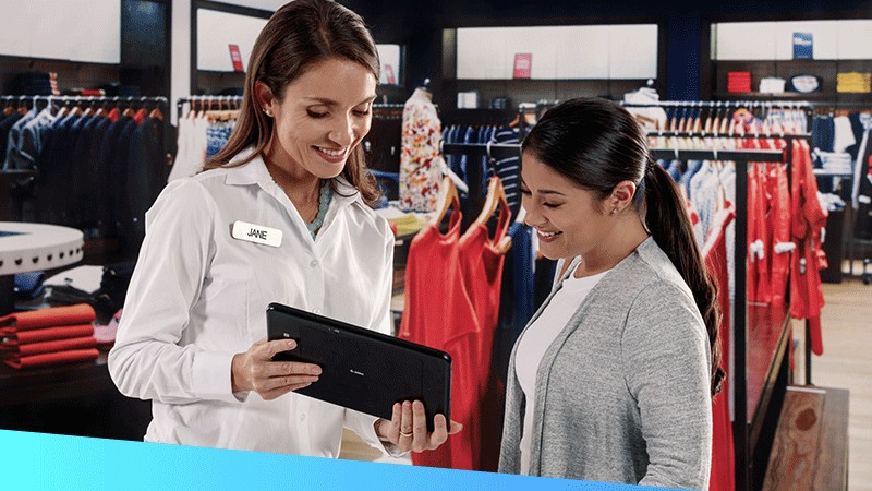 Female retail associate using rugged tablet to assist customer in apparel store