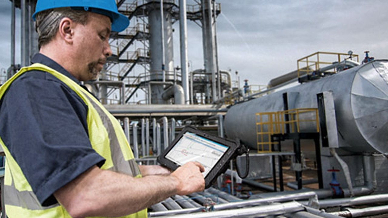 A worker uses an ATEX\u002Dcertified Zebra rugged tablet to review equipment information in a Hazardous Location