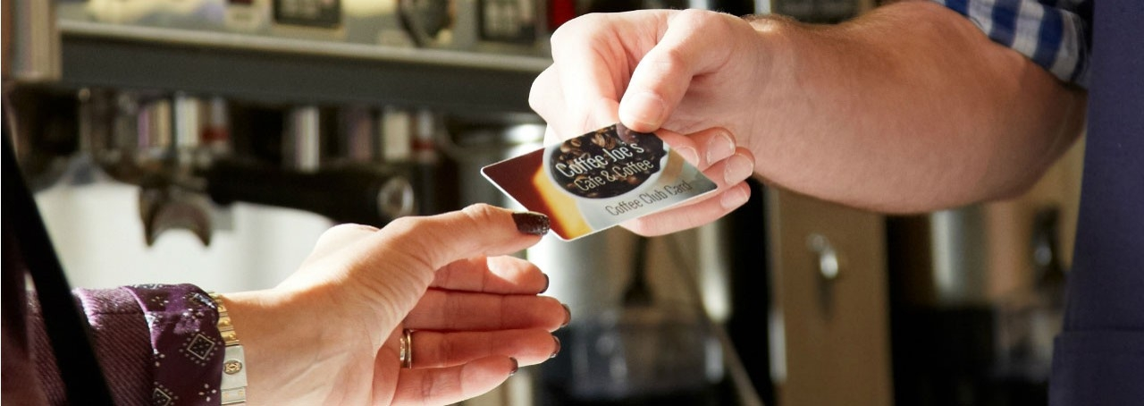 Man handing a coffee club card to a woman.