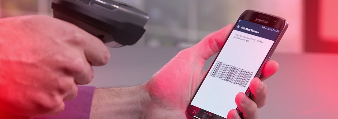 Worker using a barcode scanner to scan a barcode on a mobile device.