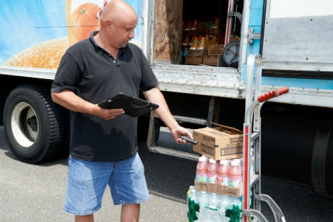 Man holding a tablet and scanning a package.