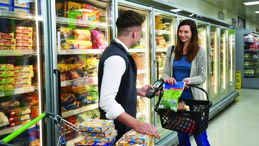 Grocery employee assisting customer with Zebra MC3300 device