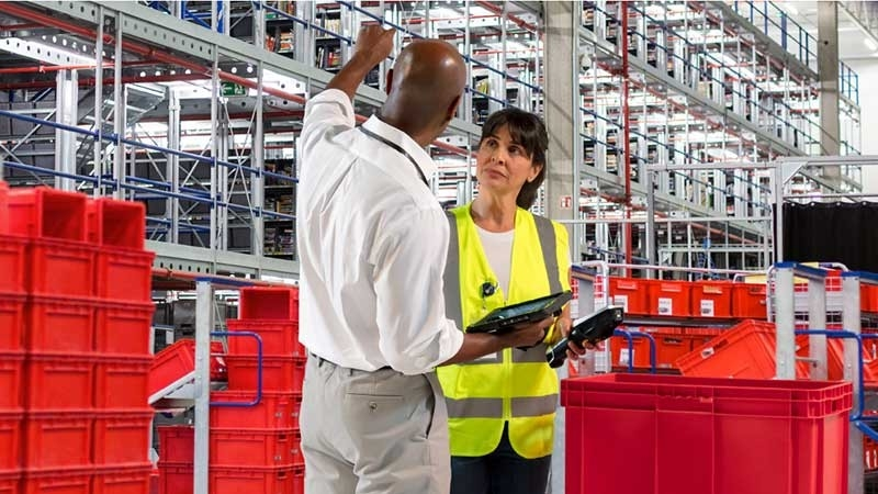 Man and women using zebra devices in warehouse