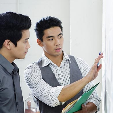 Two men working together on a graph on the wall