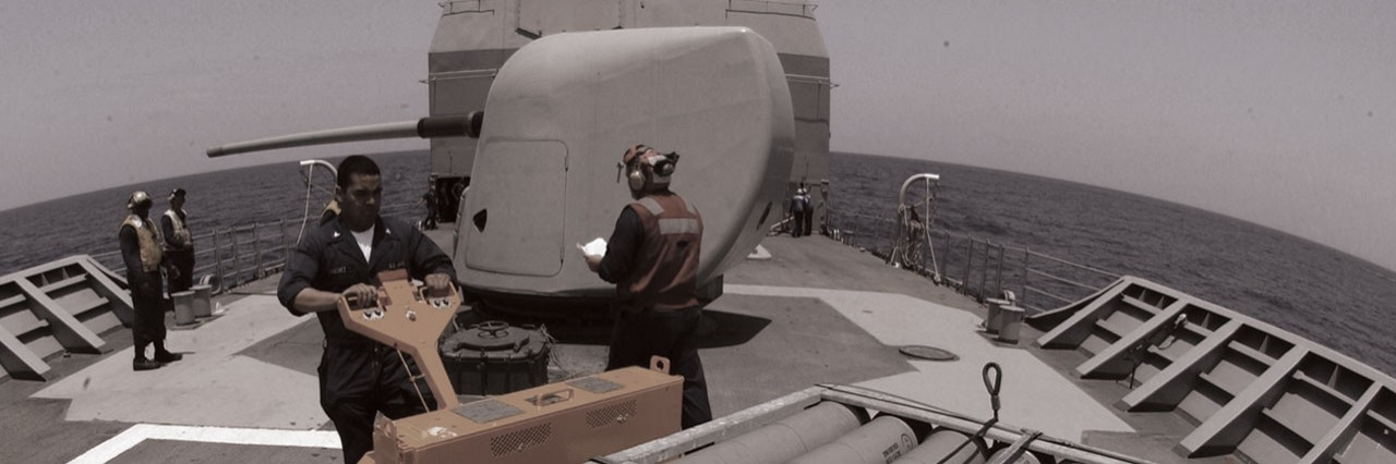 artillery maintenance on deck of naval vessel