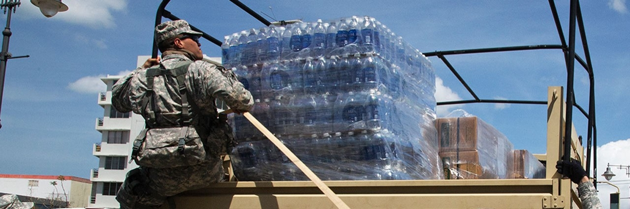 military personnel dropping off supplies to a base
