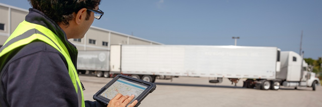 Worker using a rugged tablet to track a fleet truck en route