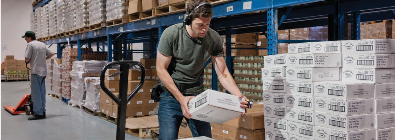 Man in warehouse wearing Zebra headset and carrying package.