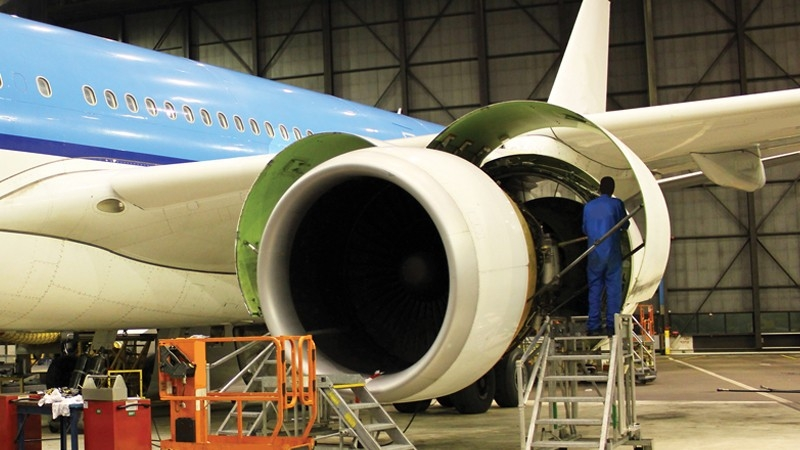 Mechanic working on fixing a jet engine.