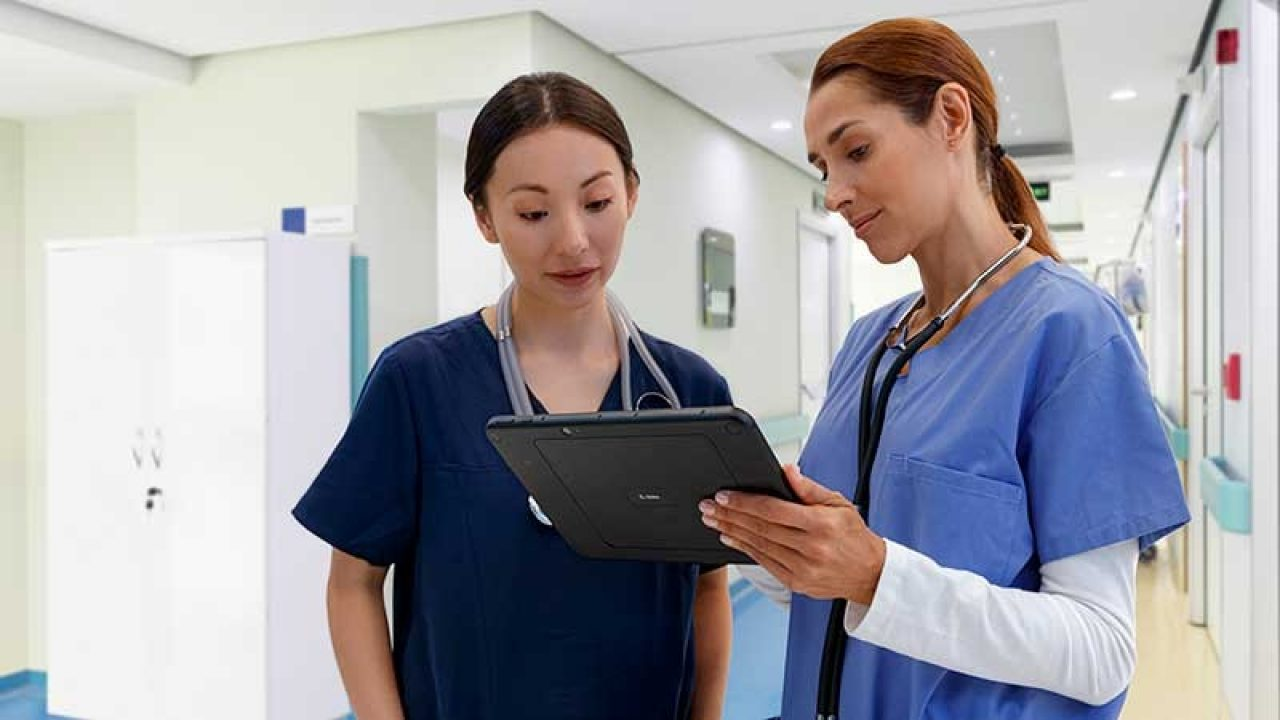 Two nurses looking at Zebra tablet in the hallway and interacting.