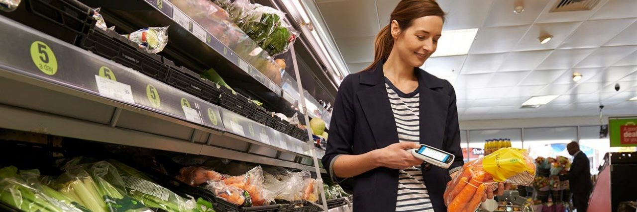 Woman in a grocery store scanning a bag of carrots with her Zebra mobile device.