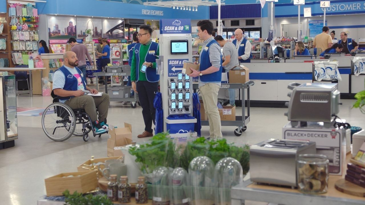 Three cast members from the American TV show Superstore hold Zebra mobile computers while standing in front of a personal shopper solution display.