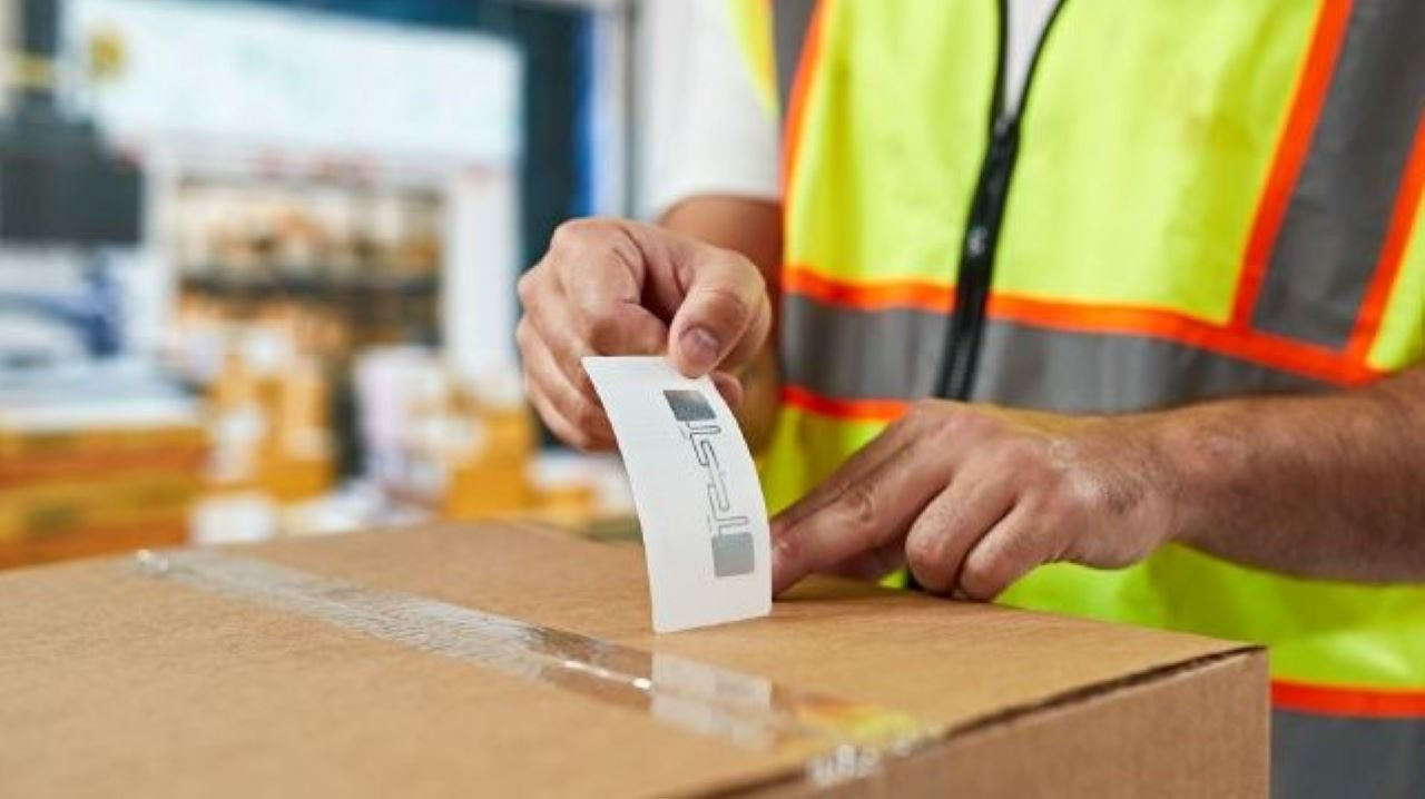 A manufacturing worker applies an RFID label to a box before it is transferred to the loading dock for shipment.