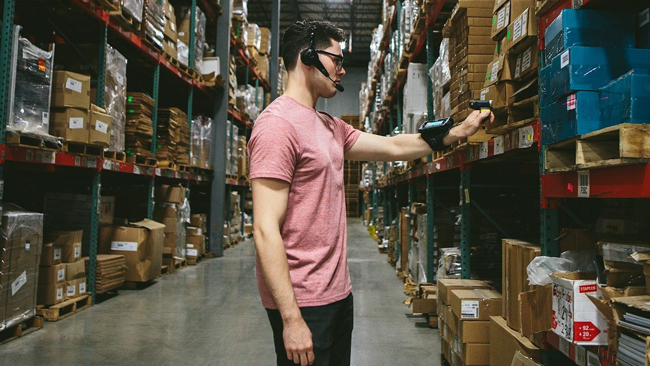 A male warehouse worker looks at a wearable on his wrist.