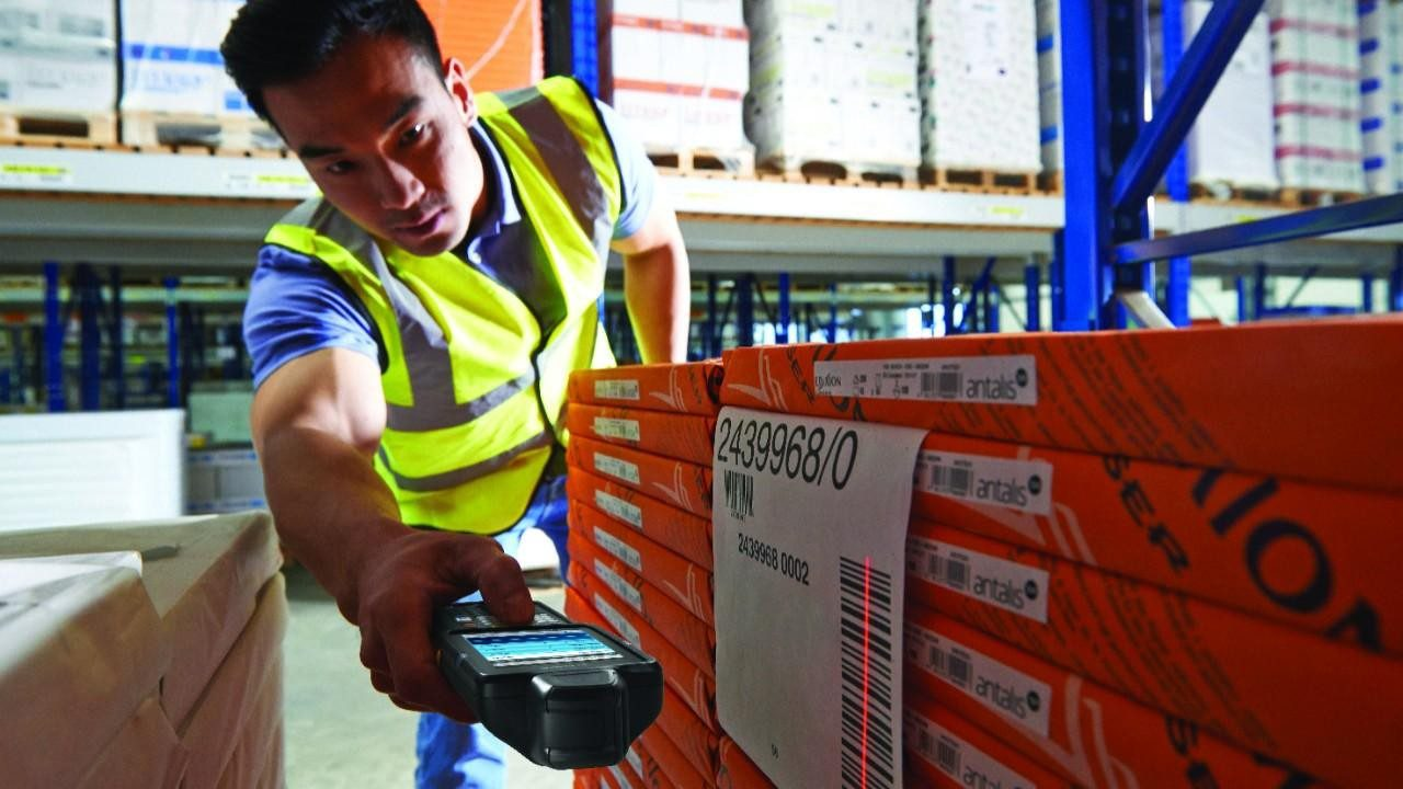 A warehouse worker uses an Android handheld mobile computer to scan the barcode on a pallet of products.