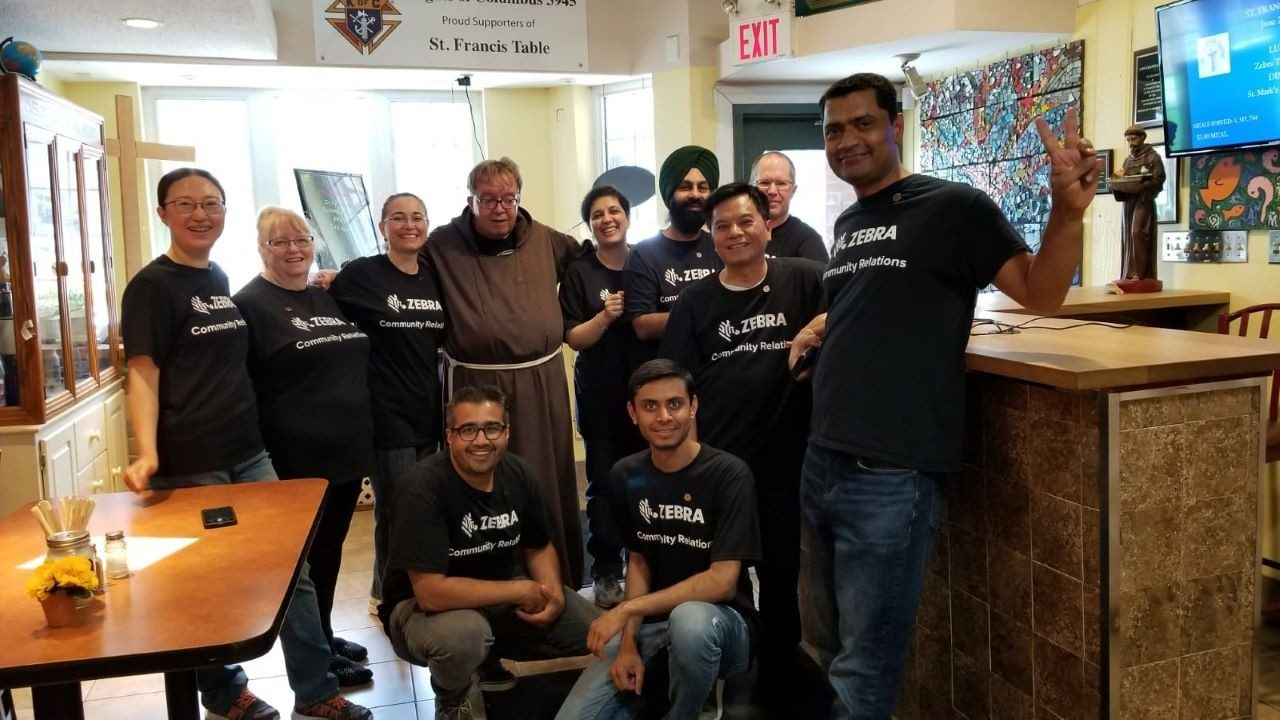 Zebra employees take a group photo with Brother John of the St. Francis Table soup kitchen in Mississauga after volunteering for the day. From left, Leah Li, Sharon Owen, Ozlem Seri, Brother John from St. Francis Table, Persis Daver, Gurjit Matharoo, Dave Lawson, Lawrence Lam, Dharmajit Solanki, Ali Saifuddin \x26amp; Kushal Sakhia.