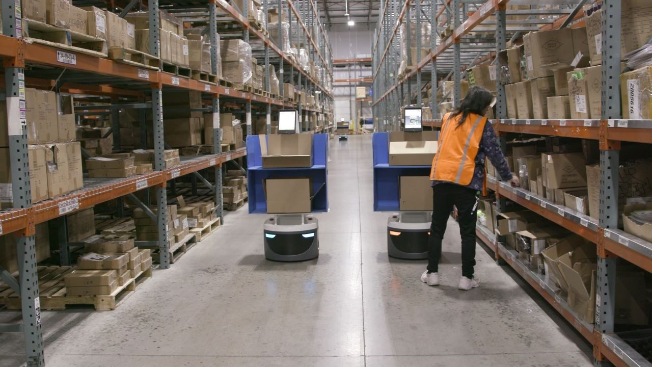 A worker collaborates with a Locus Robotics co\u002Dbot to pick inventory in a warehouse