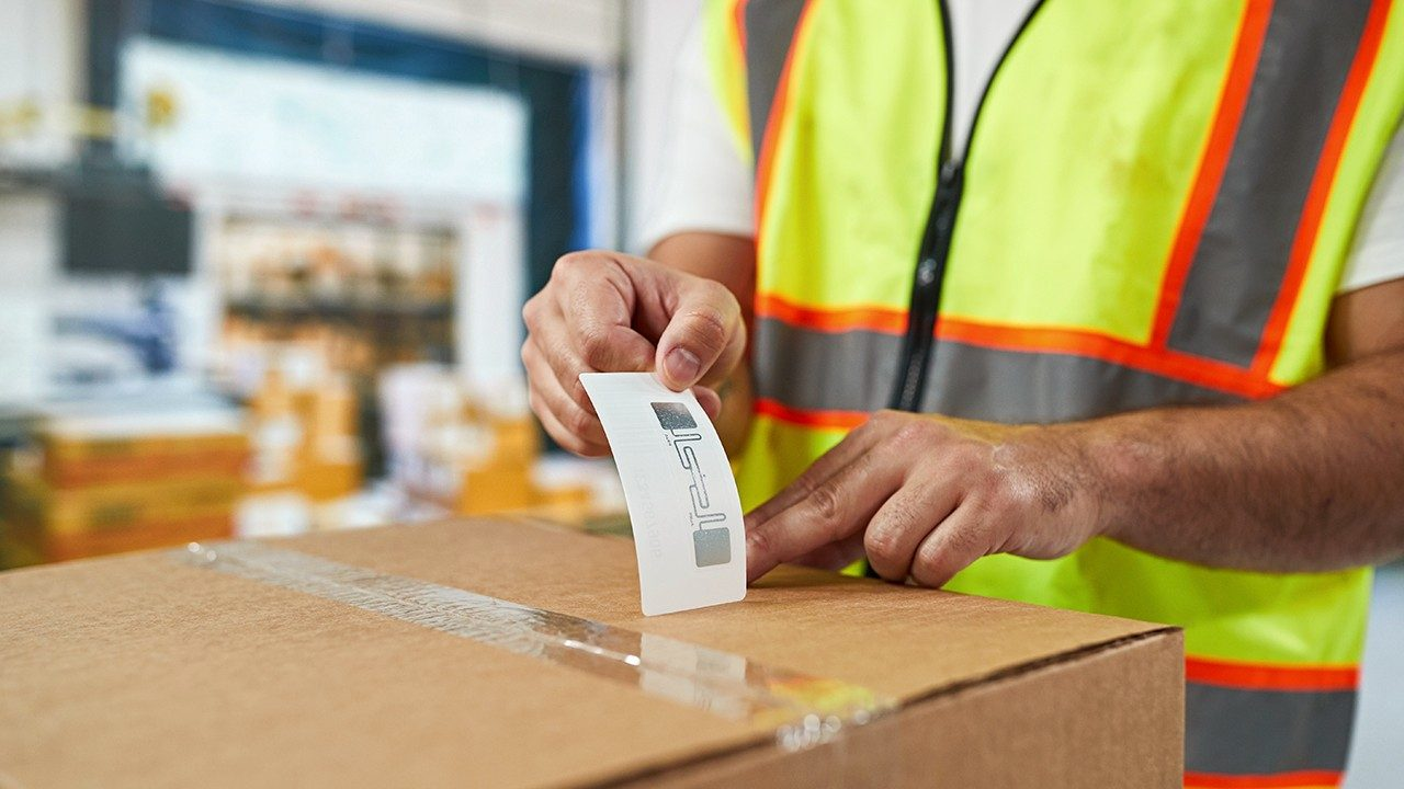 A warehouse worker applies an RFID label to a box