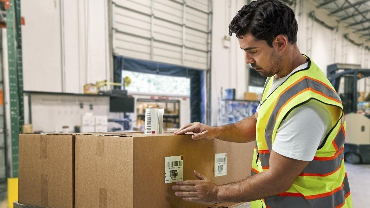 A warehouse worker applies a barcode label to a box in preparation for shipment