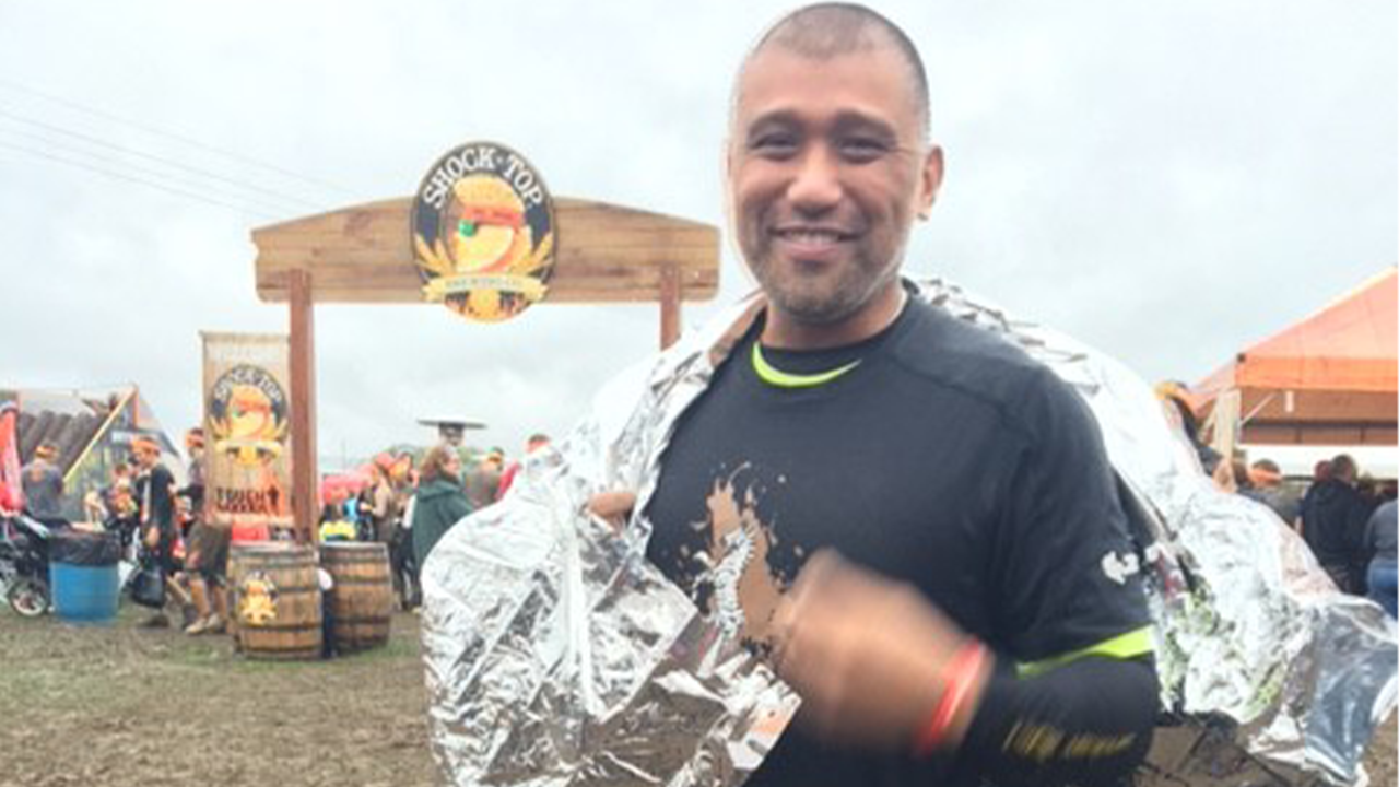 Jay Alfonso stands behind the finish line after completing a Tough Mudder competition.