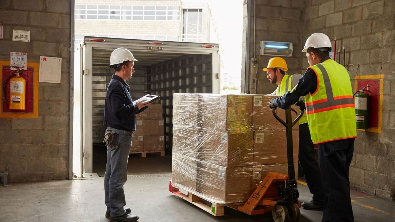 Workers prepare to load a pallet from a warehouse onto a truck while a supervisor documents the action on a rugged tablet.