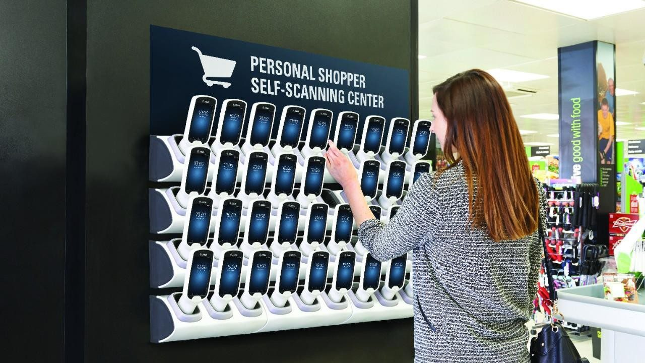 A woman grabs a smartphone from the Personal Shopping Solution display in a retail store.