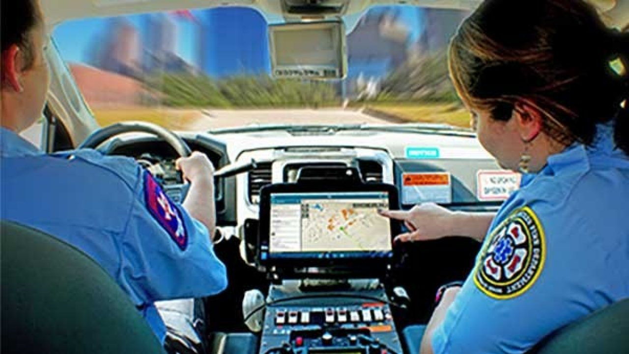 Two EMS technicians look at a Zebra XSLATE R12 rugged tablet mounted in their ambulance to get directions to a call.