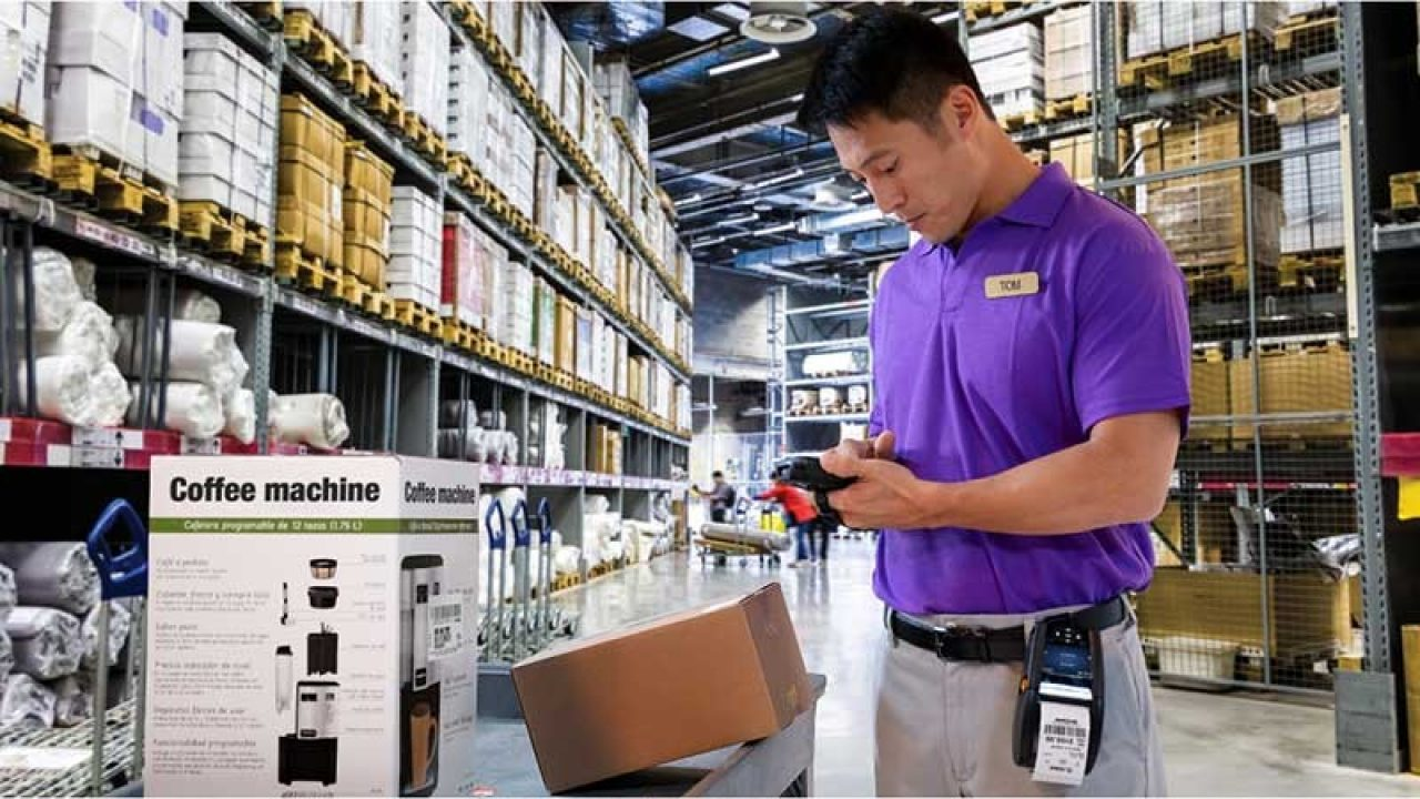 A male warehouse worker uses mobile computers to pick the right products and fulfill an order.