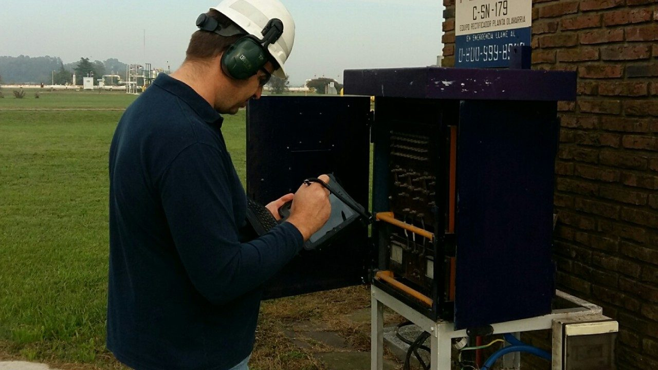 A TGS worker looks at a Zebra rugged tablet while servicing a piece of equipment in the field