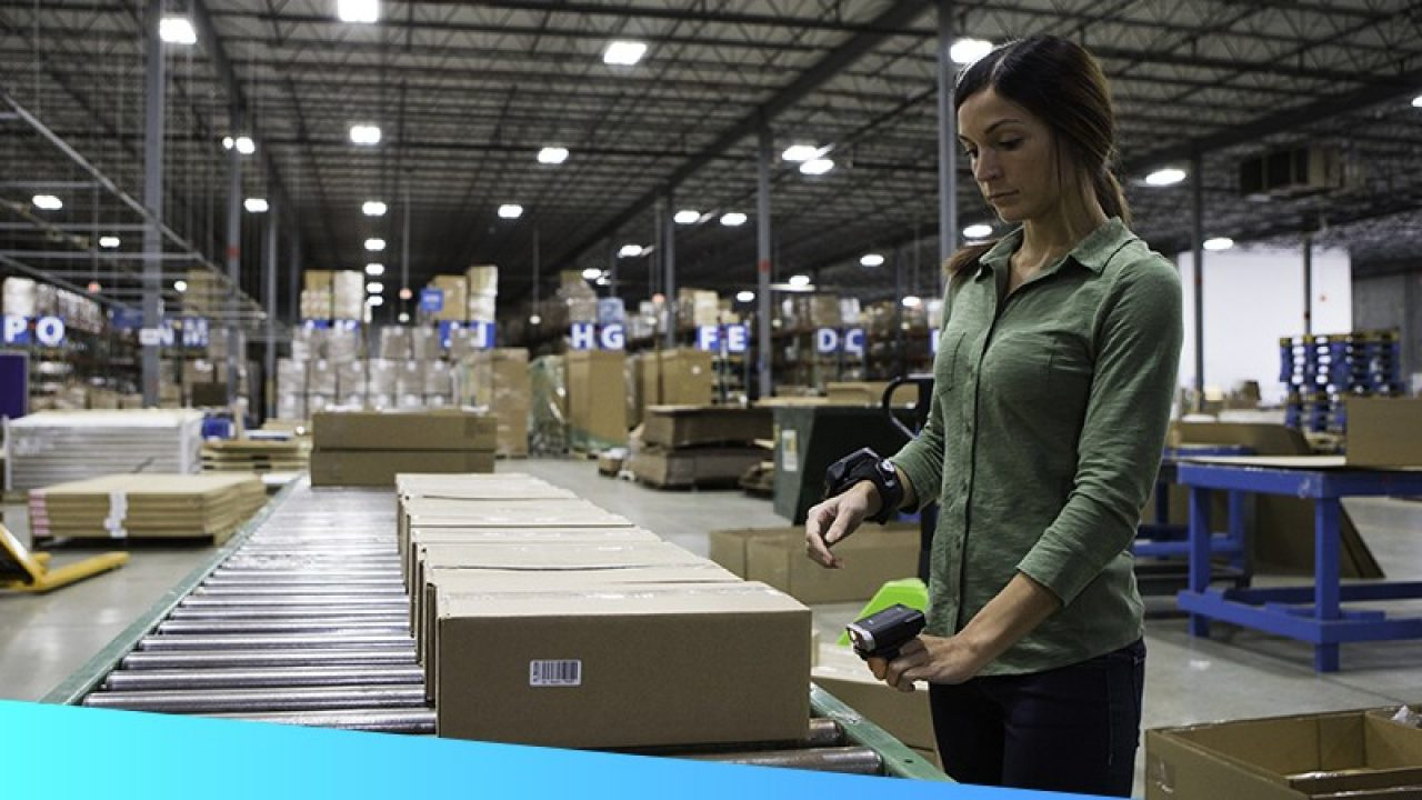 A woman processes a package in a dimly lit warehouse.