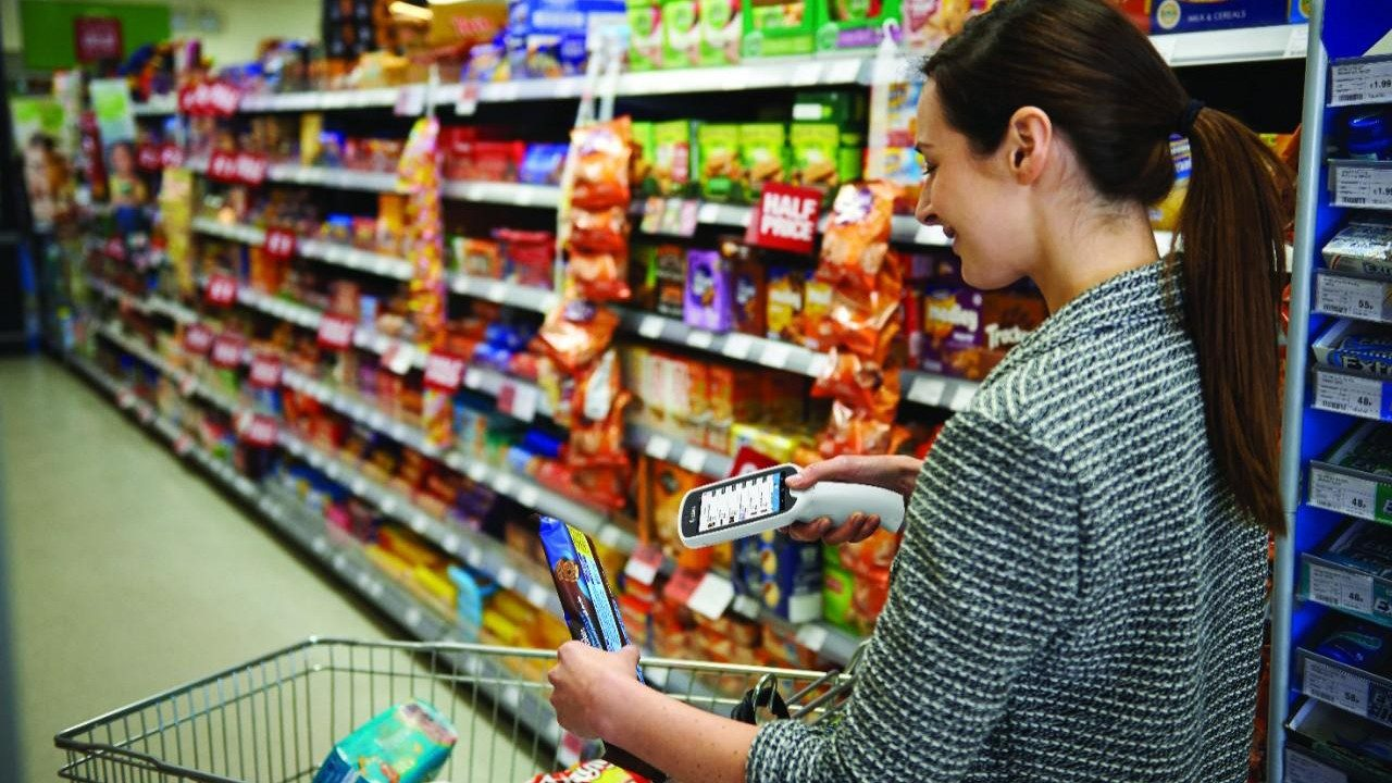 A female shopper use a smartphone to scan an item in a grocery store