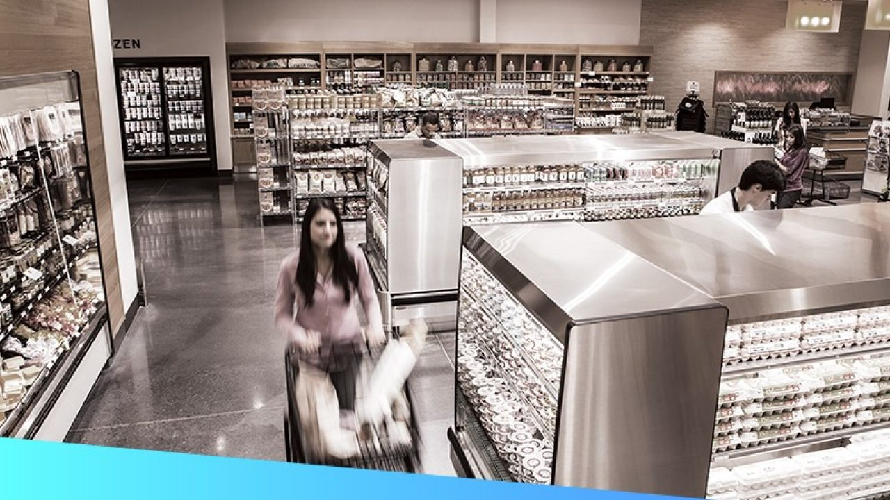 Shoppers walk through a grocery store while keeping social distance