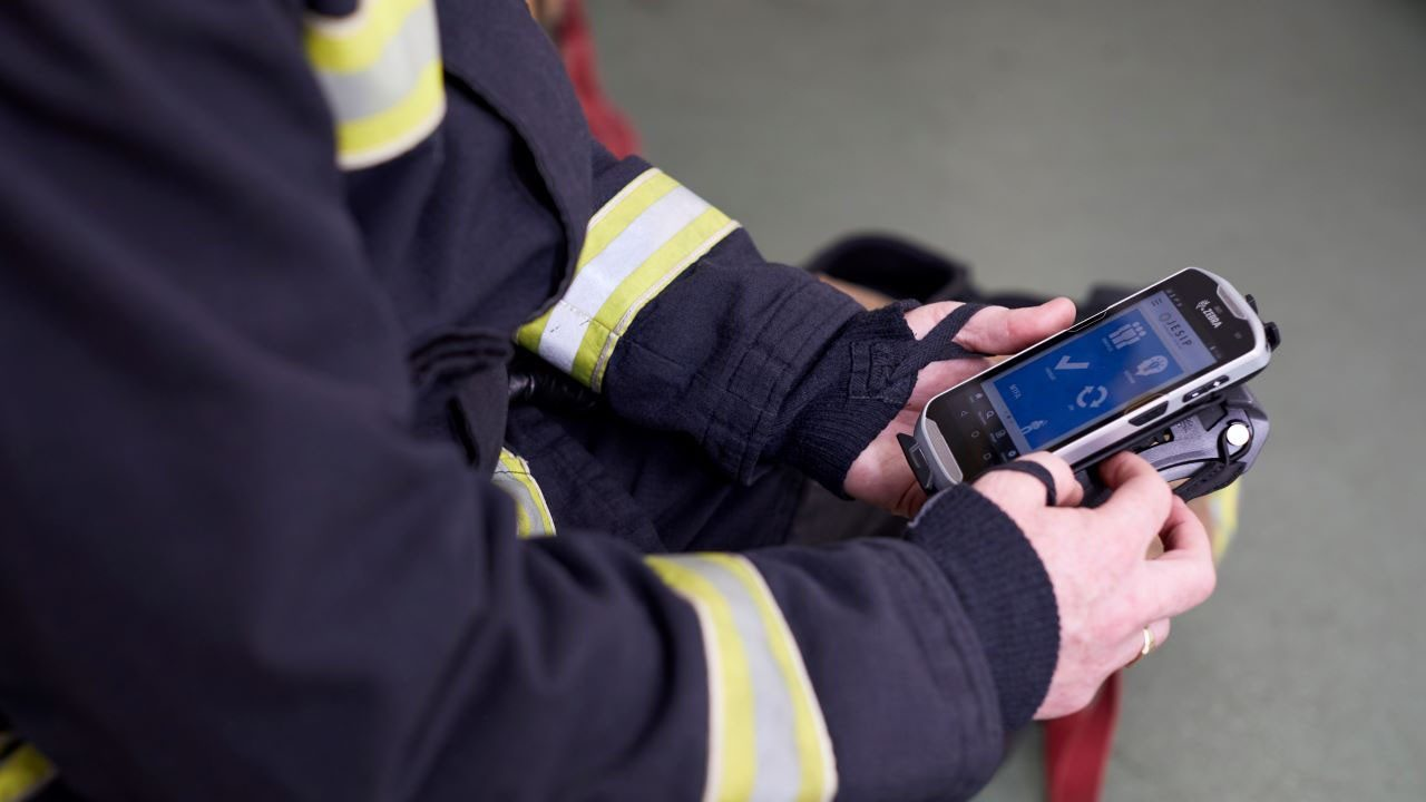 A firefighter looks at the screen of a Zebra TC52 mobile computer.
