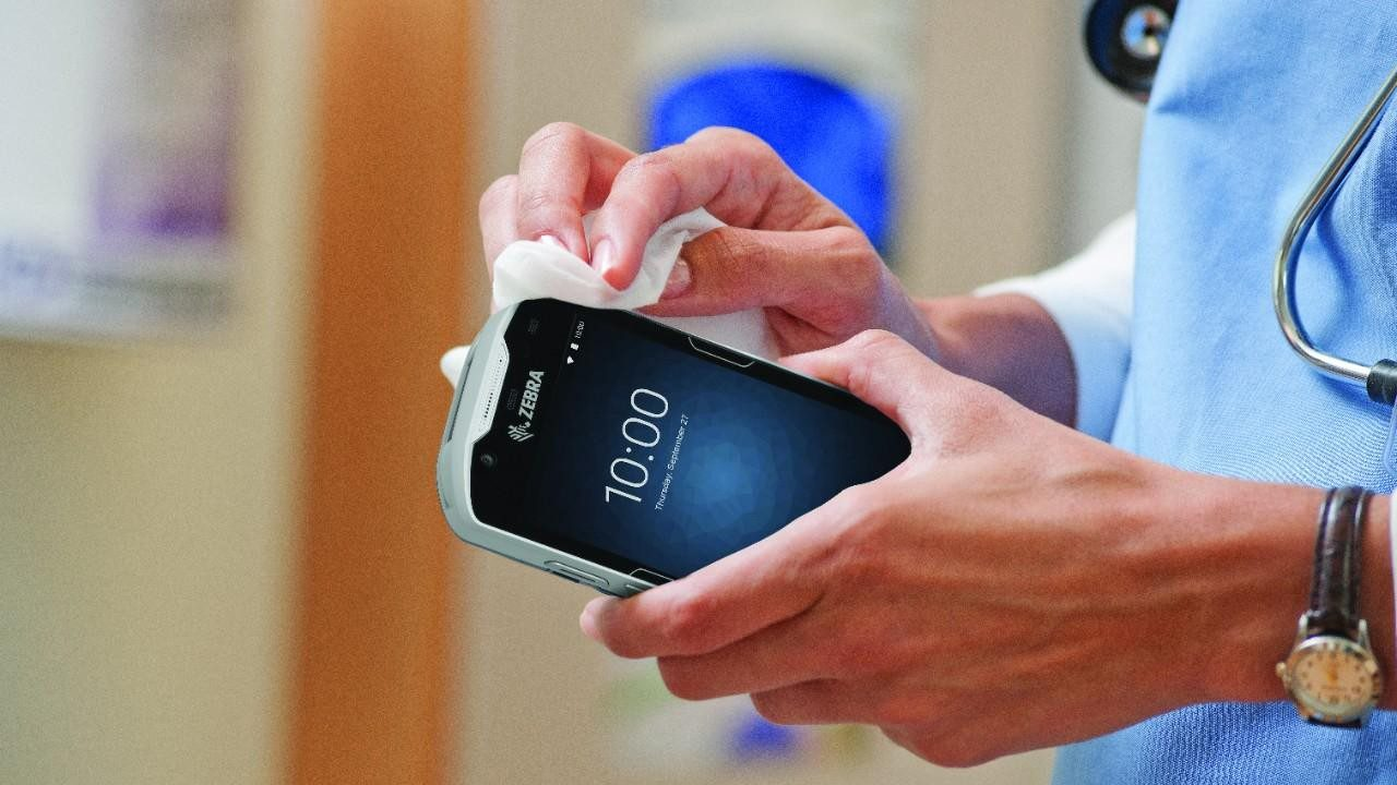 A healthcare provider disinfects a Zebra clinical smartphone