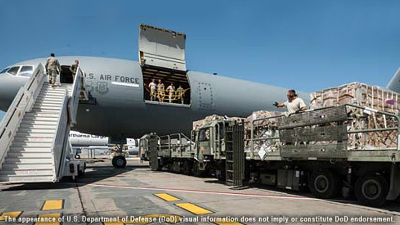 A U..S. Air Force cargo plane is loaded with equipment and pallets on a tarmac