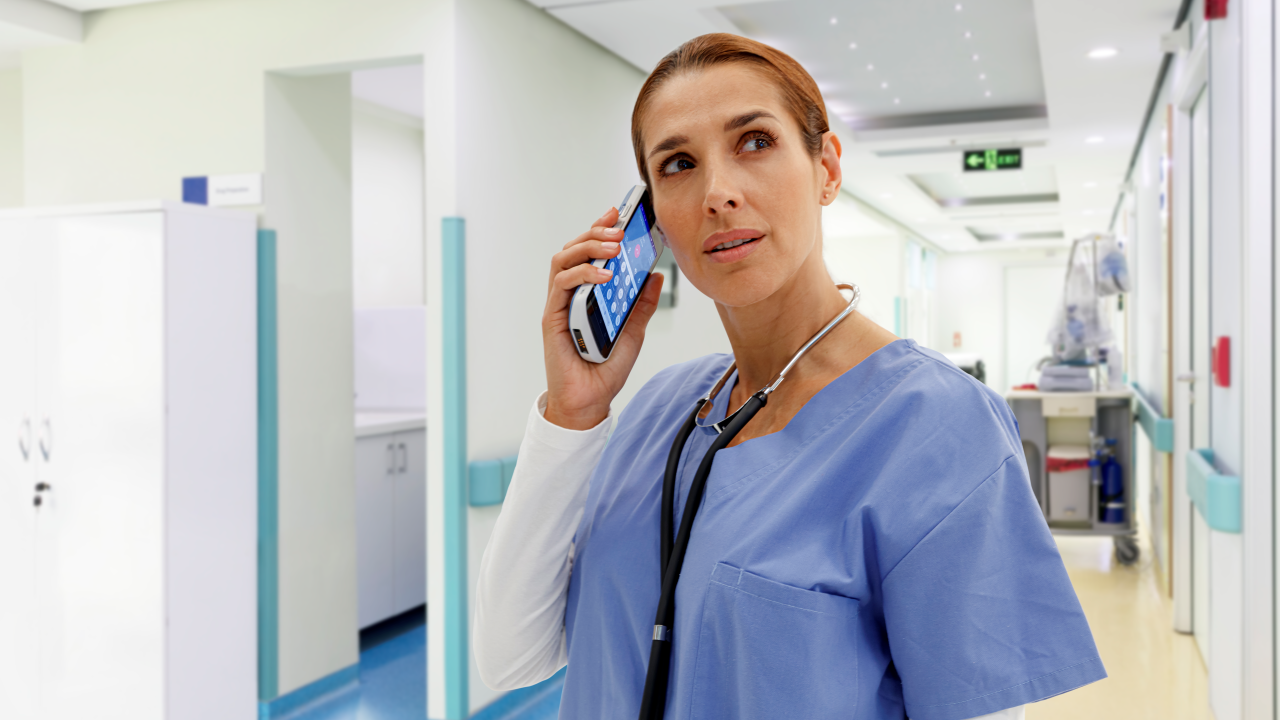 A nurse uses a clinical smartphone to call another care team member in a hospital hallway