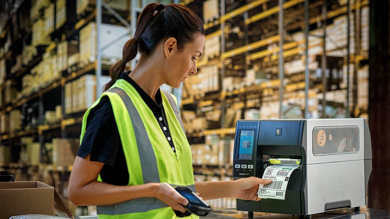 A female warehouse worker grabs a label off an industrial printer