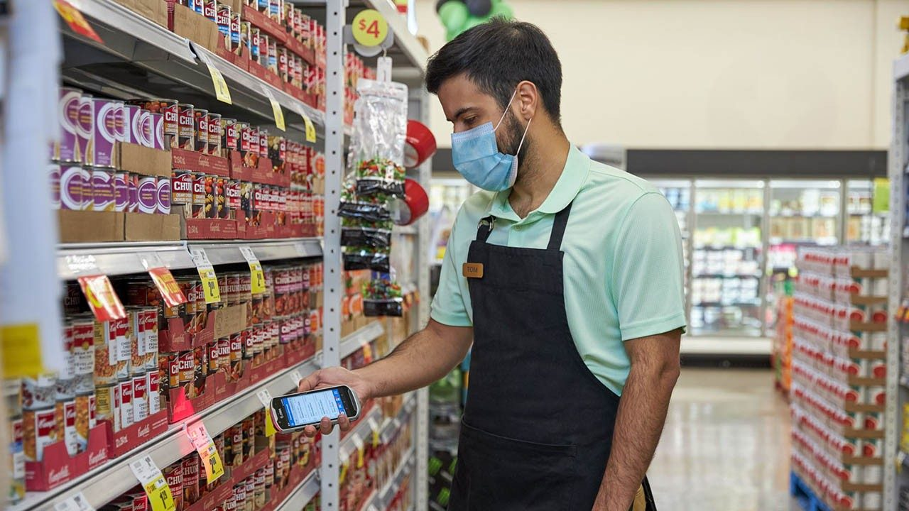 A retail store associate uses a handheld mobile computer to scan shelf inventory tags