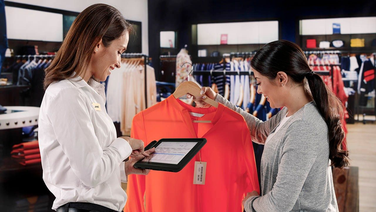 The Zebra ET51 Android rugged tablet with integrated scanner is used by a retail store associate to help checkout a customer via mobile point of sale