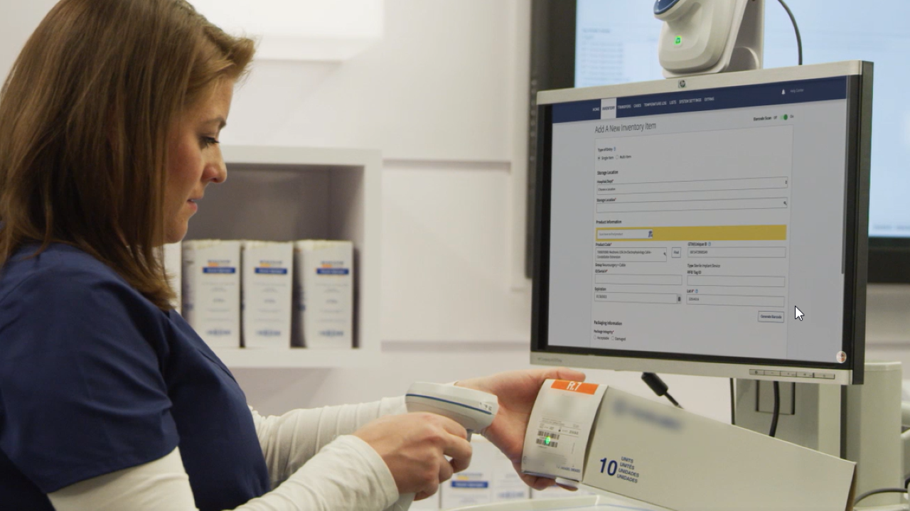 A nurse uses a barcode scanner to capture UDI label data from the packaging of a medical device.