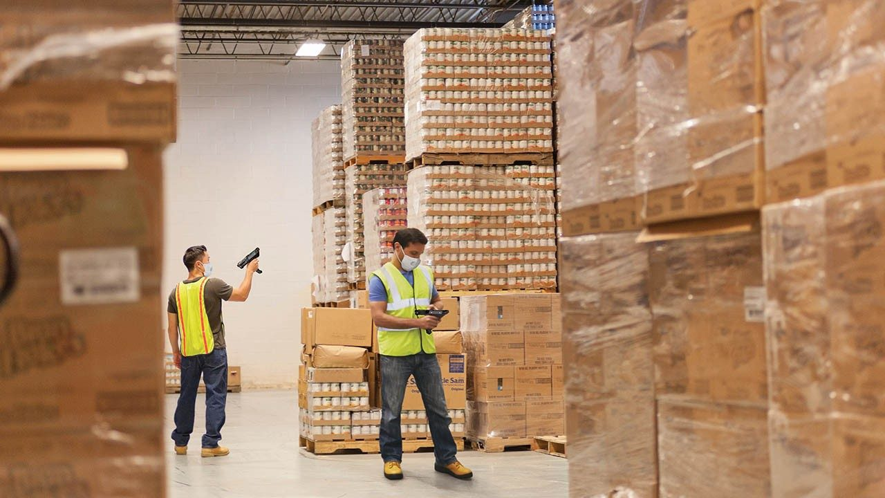 Two warehouse workers scan inventory while maintaining social distance