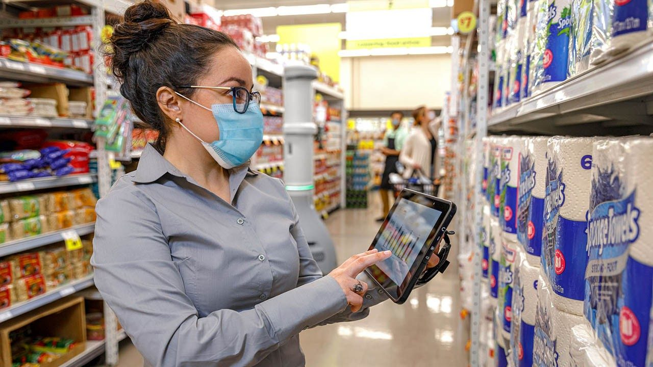 A grocery store manager reviews shelf inventory information on her rugged tablet in the toilet paper aisle