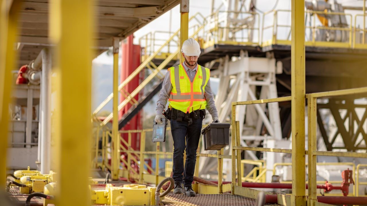 A utility field worker walks across a catwalk carrying a toolbox in one hand and a Zebra XSLATE L10 rugged tablet in the other.