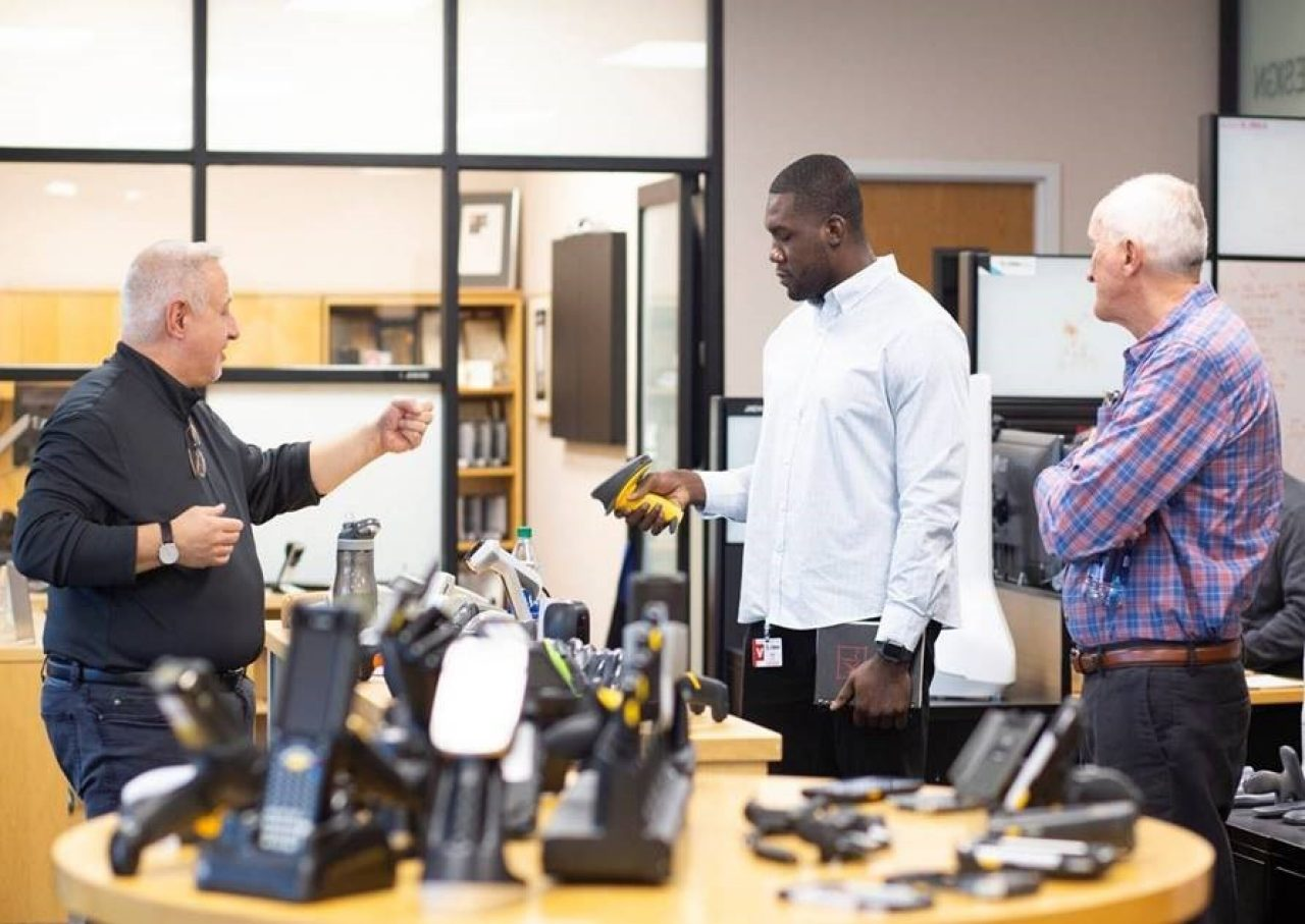 NFL defensive lineman Eric Lee get a hands\u002Don demo of Zebra technology at the Holtsville office during hs three\u002Dweek externship