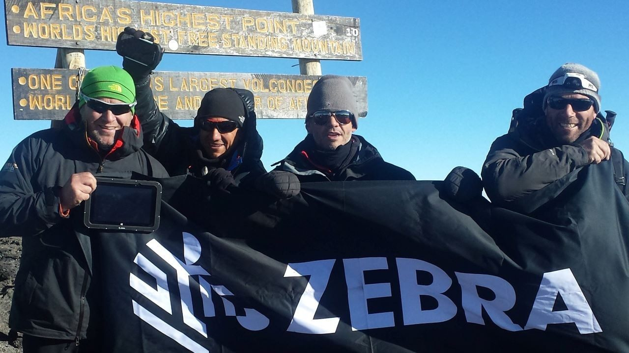 Three Zebra employees and a friend at the top of Mount Kilimanjaro.