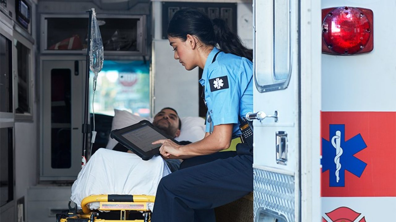 Emergency medical technician using a Zebra tablet in an ambulance