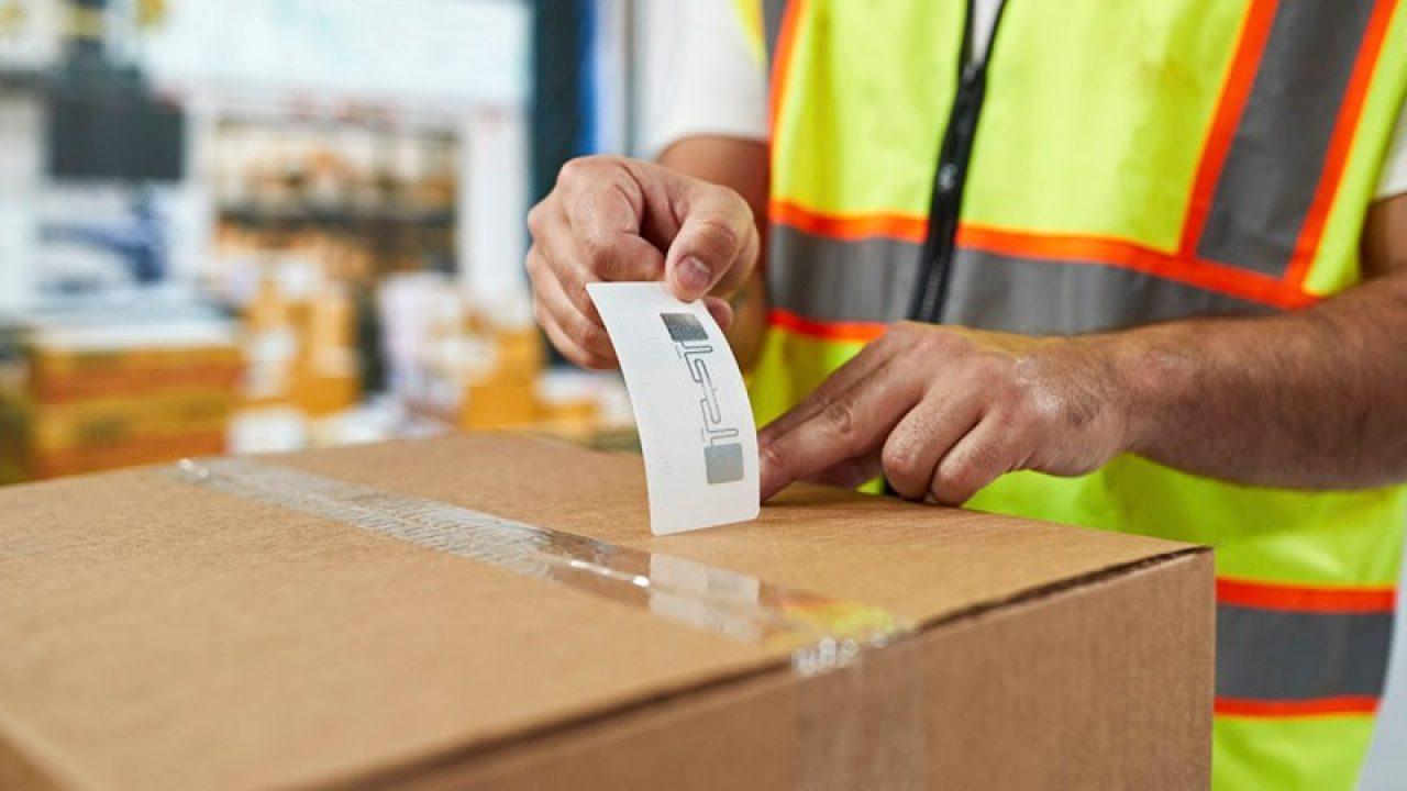 RFID label being placed on a box in a warehouse