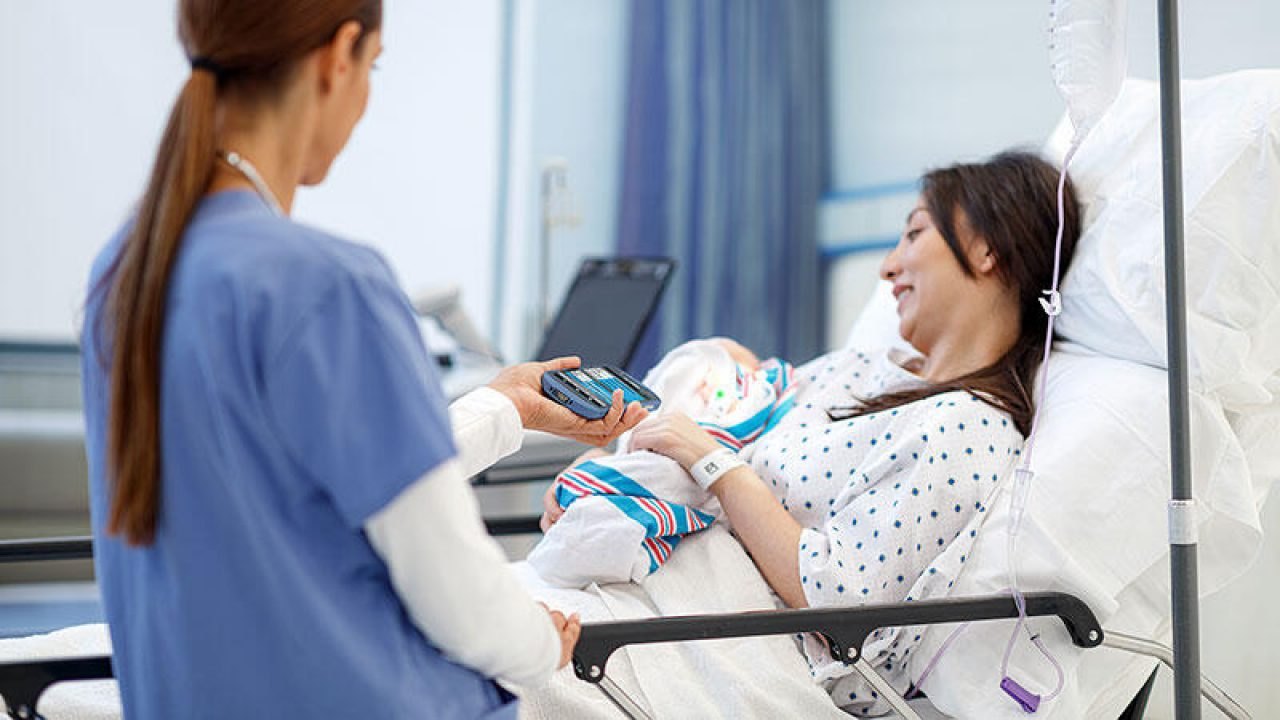 Woman in hospital bed having her wristband scanned.