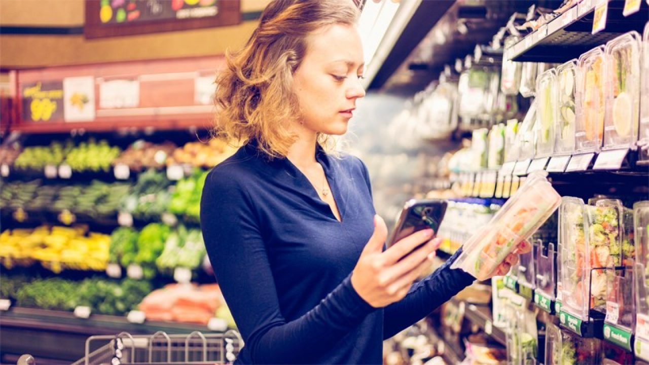 woman with cell phone in hand looking at packaged food in grocery store