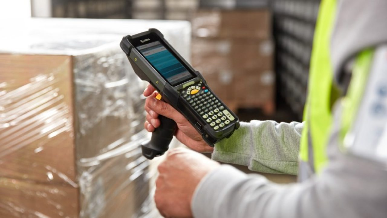 Handheld Mobile Computer being held by warehouse worker
